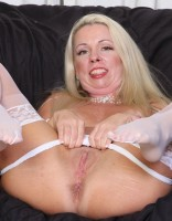 Blonde mature Liz in white stockings takes off her panties to play with her shaved pussy